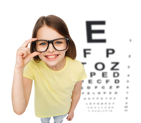 people, childhood, healthcare and vision concept - smiling little girl in black eyeglasses over white background with eye chart